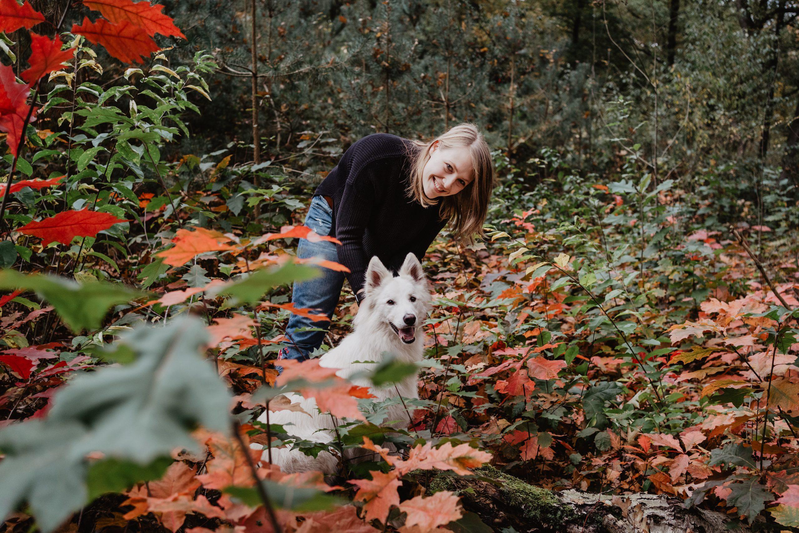 hondengedragscoach Lisse van de Groep met haar witte herder in het bos met herfstkleuren